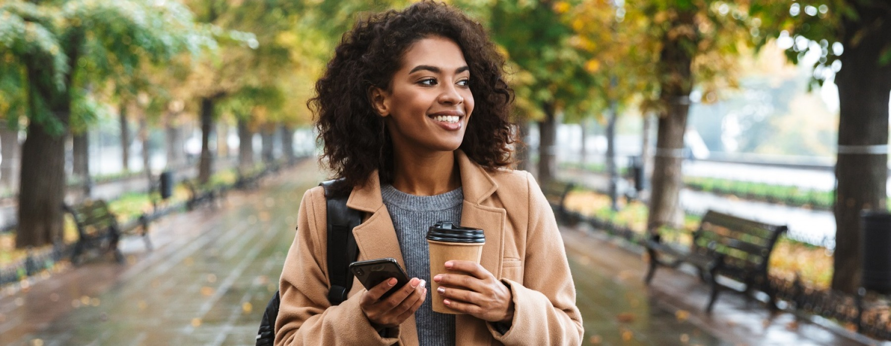 Woman walking in Park holding her Coffee